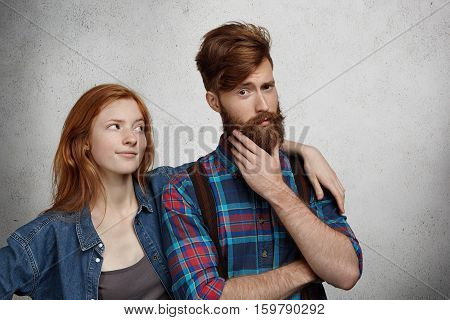 Relationship Problems Concept. Young Couple Quarelling Indoors. Redhead Woman Feeling Mad At Her Hip