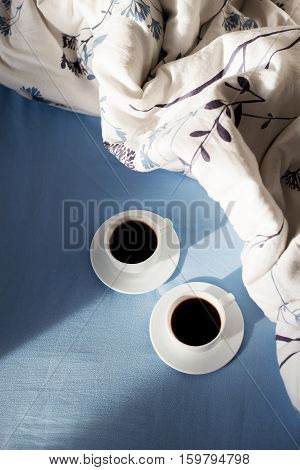 two cups of coffee in bed, sunlight