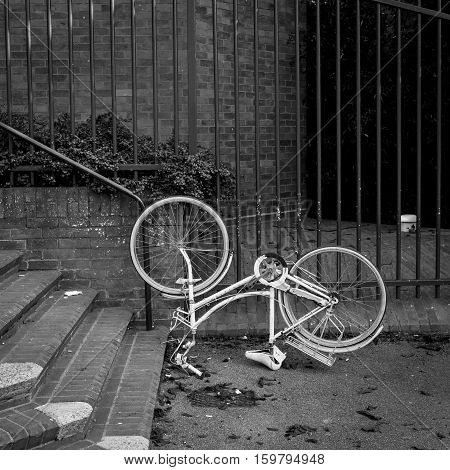 Mansfield Road Oxford United Kingdom October 23 2016: Upside-down white city bicycle in front of the metal fence on Mansfield Road Oxford.