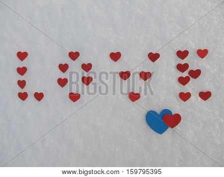The word love from red hearts in the snow in winter, Valentine