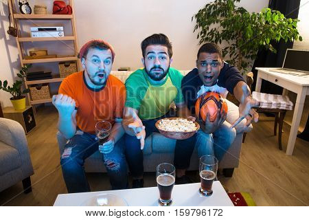 Image of funne friends watching football game on TV and waiting for exciting and amazing moments from foolball players.