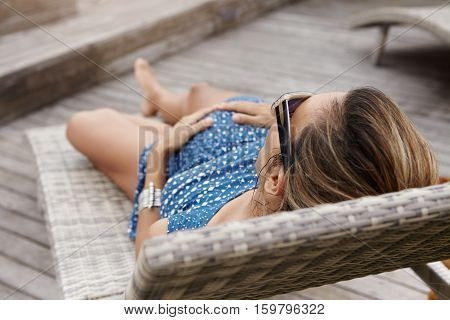 Pregnancy And Maternity Concept. Outdoor Shot Of Pregnant Female Having Rest, Lying On Lounger At He