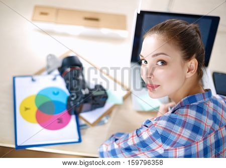 Female photographer sitting on the desk with laptop .
