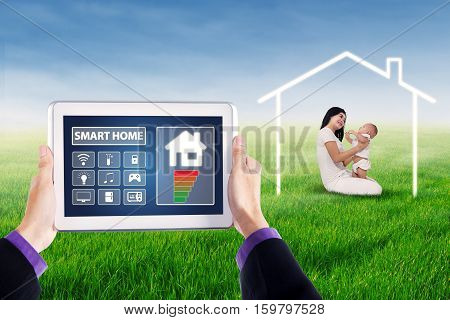 Application icons of smart house system on the digital tablet screen with happy mother and her baby playing on the meadow under a smart house symbol