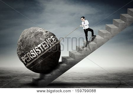 Photo of a little boy climbing up a stairway while pulling a big stone with persistence word