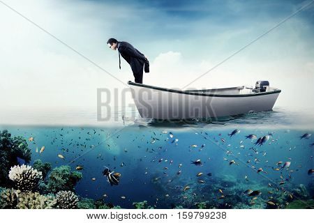 Photo of a young businessman standing on the boat and looking down at the sea
