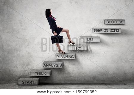 Young busineswoman carrying a briefcase and climbing a ladder with strategy texts toward success