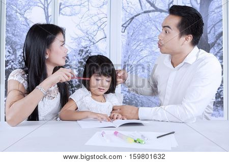 Portrait of a crying female child while studying with her parents quarreling at home