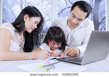 Little girl doing homework with her parents while using a laptop and write on the book at home