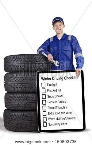 Portrait of a male mechanic holding a wrench and showing tips of winter driving while standing with tyres isolated on white background