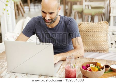 Good-looking Adult Man With Beard Checking E-mail On Laptop, Using Free Wireless Internet Connection