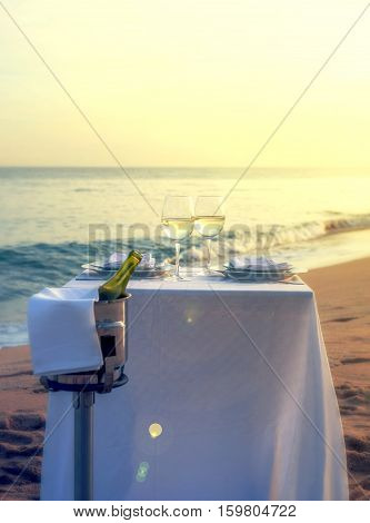 A romantic restaurant table on a beach on a summer evening.