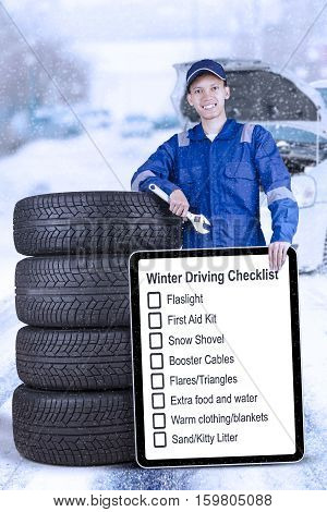 Portrait of a male technician holding a wrench and showing tips of winter driving while standing with tyres in the outdoors