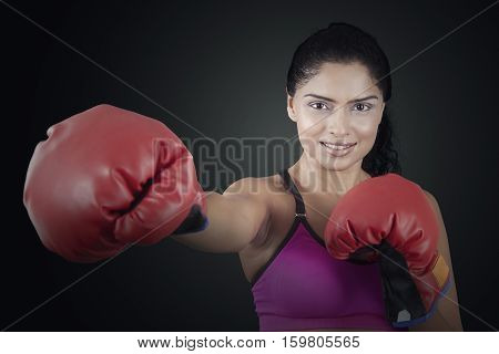 Portrait of attractive woman with red boxing gloves and throw a punch into the air on the black background