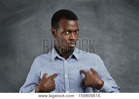 Headshot Of Young Dark-skinned Man Pointing At Himself, Making Excuses Or Verbally Defending, Having