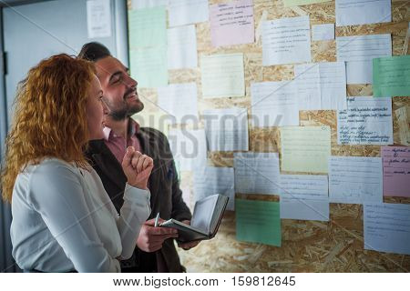 Happy businessman and businesswoman communicating near notice board and deciding when to conduct meeting for Board or Directors in office interior.