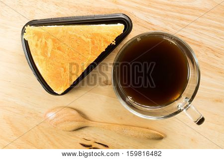 Foi thong cake and a cup of coffee on wooden board
