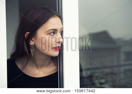 portrait of beautiful brunette young woman looking out of window