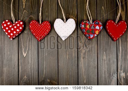 Five Red And White Hearts Lie On A Wooden Surface