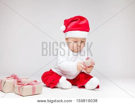 Adorable Baby Wearing A Santa Hat Opening Christmas Presents