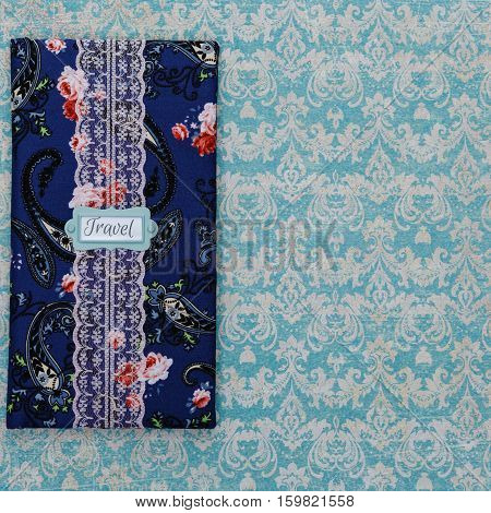 Beautiful handmade scrapbooking holder for travel documents with lace detail and ribbon closure lying on paper with damask print. Floral fabric design. Copy space. Square composition.