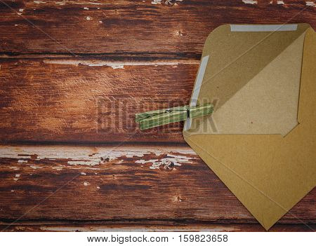 Opened vintage envelope with wooden pin lying on rough wood. Copy space.