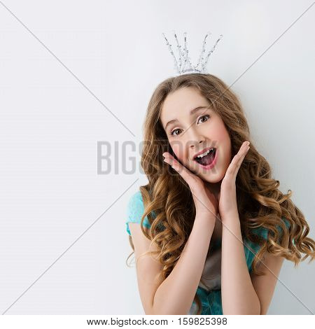 Happy teenage girl with long curly hair and crown on head looking like princess. Surprised expression. Studio portrait on light background. Copy space. Square composition.
