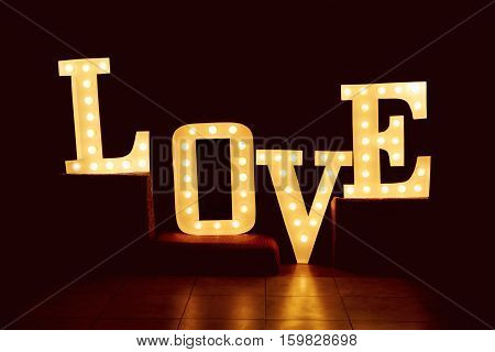 word love from big letters with glowing light bulbs on a dark background