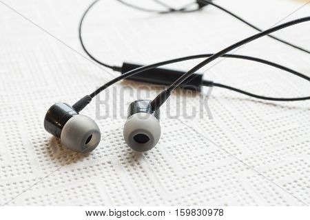 Black Earphone or earphones on white background. Black earphones for using digital music or smart phone. Earbuds isolated.