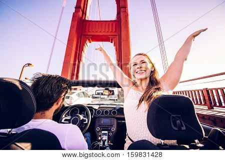 Happy couple driving on a convertible car - Road trip to San Francisco woman with raised arms greeting Golden Gate Bridge