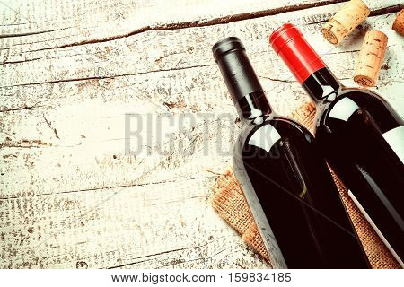 Setting with bottles of red wine and corks. Wine list concept with copy space