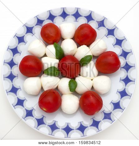 Mozzarella with tomatoes and basil on white background