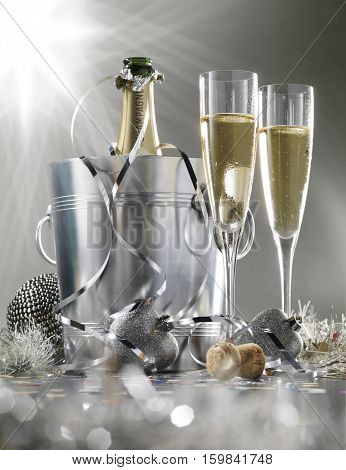 Two glasses of champagne with bottle in cooler on a silver background selective focus