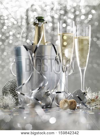 Two glasses of champagne with bottle in cooler on a silver bokeh background