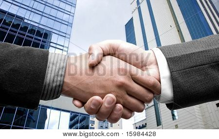 e-commerce handshake and business city buildings in the background