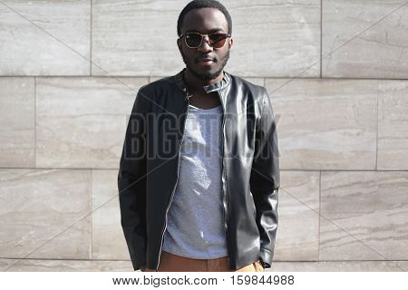 Fashion African Man Wearing A Sunglasses And Black Rock Leather Jacket Over Textured Gray Background