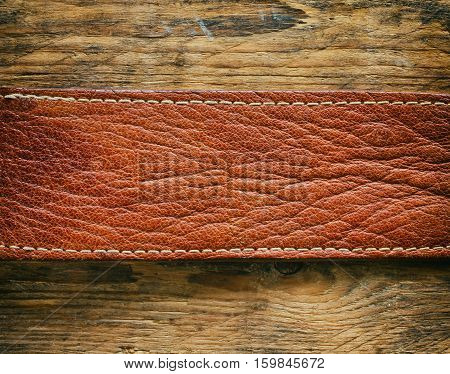 detail texture natural brown leather belt on a wooden old table