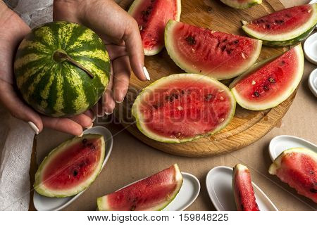 Watermelon salad. Slices of watermelon in the shape of a star. Children's hands cooking fruit salad on white table. Top view flat lay