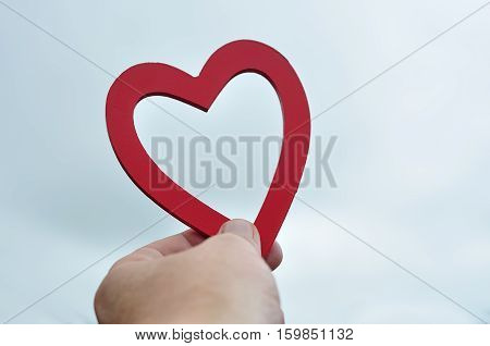 A mans hand holding a red wooden heart up against the sky