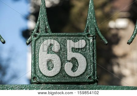 Old retro weathered cast iron plate with number 65