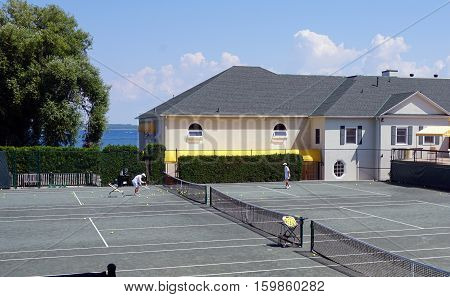 HARBOR POINT, MICHIGAN / UNITED STATES - AUGUST 3, 2016: Two men enjoy playing tennis at the Little Harbor Club.