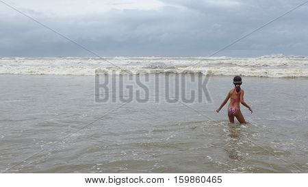 Girl waiting for waves to break at seashore