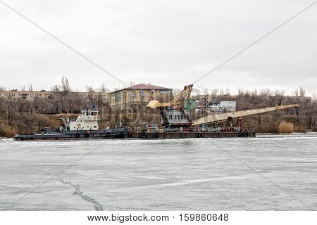 River Tug Pusher Drags A Floating Crane On A Ship Canal Through The Ice