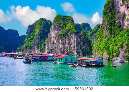 Floating fishing village rock island in Halong Bay Vietnam Southeast Asia. UNESCO World Heritage Site. Junk boat cruise to Ha Long Bay. Landscape. Popular asian landmark famous destination of Vietnam