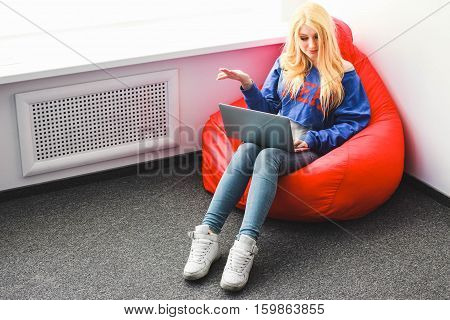 Blonde with a laptop outraged sitting on a chair-sac