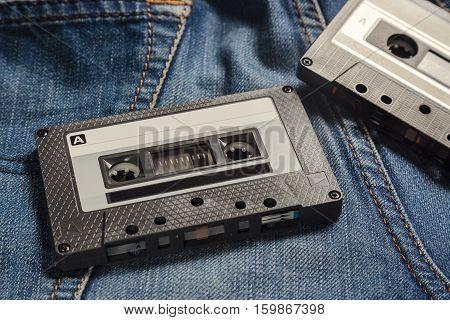 Audio Tape Cassettes on the blue jeans. Vintage toned image