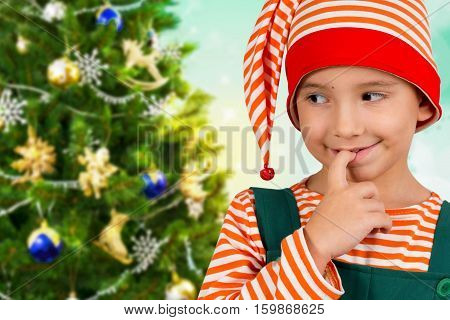 Portrait of a child in an elf suit on the background of Christmas tree