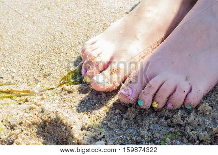 Well cared women feet with colorful nail polish on beach