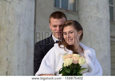 Happy wedding couple with bunch of flowers.