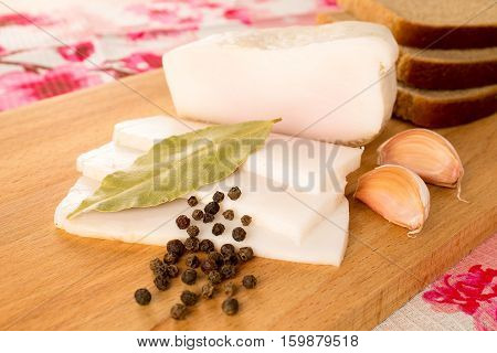 salo, becon with bread, pepper and garlic on the table